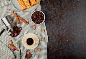 bovenaanzicht van een kopje koffie en kaneelstokjes