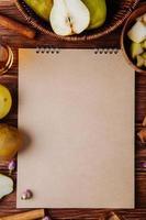 bovenaanzicht van een schetsboek en verse rijpe peren op houten achtergrond foto