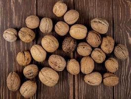bovenaanzicht van hele walnoten verspreid over houten achtergrond foto