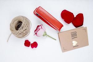 bovenaanzicht van touw met rozenblaadjes en een kleine ansichtkaart foto