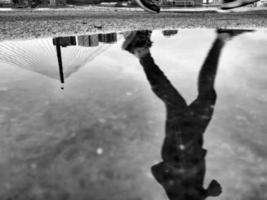 plas weerspiegeling van een man die rent