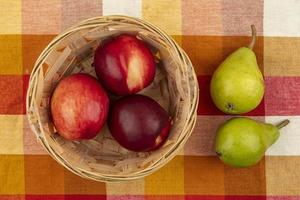 bovenaanzicht van perziken in mand en peren op geruite doek achtergrond