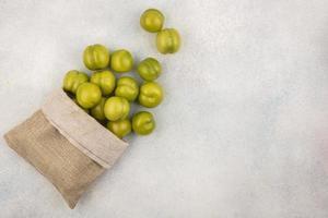 bovenaanzicht van groene pruimen die uit de zak morsen