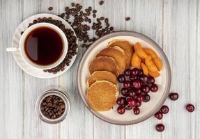 bovenaanzicht van pannenkoeken met kersen en abrikozenplakken