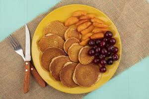 bovenaanzicht van pannenkoeken met kersen en abrikozenplakken foto