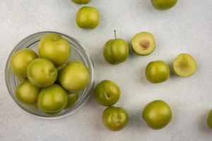 bovenaanzicht van groene pruimen in pot en op witte achtergrond foto