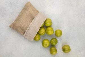 bovenaanzicht van groene pruimen morsen uit zak op witte achtergrond foto