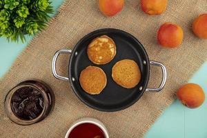 bovenaanzicht van pannenkoeken in pan en aardbeienjam