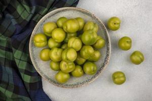 bovenaanzicht van groene pruimen op geruite doek en op witte achtergrond