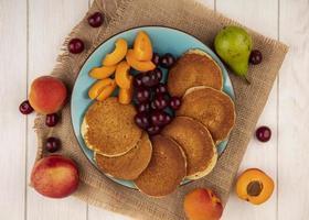 bovenaanzicht van pannenkoeken met kersen en abrikoos foto
