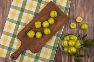 bovenaanzicht van groene pruimen op snijplank foto