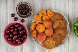 bovenaanzicht van pannenkoeken met hele en gesneden abrikozen foto