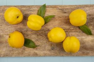 bovenaanzicht van verse gele perziken met bladeren geïsoleerd op een houten keukenbord op een blauwe achtergrond