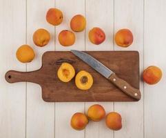 bovenaanzicht van half gesneden abrikoos met mes foto