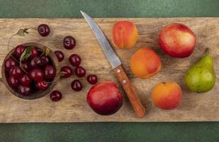 bovenaanzicht van fruit op snijplank op groene achtergrond