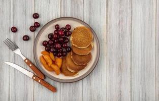 bovenaanzicht van pannenkoeken met plakjes abrikoos en kersen foto