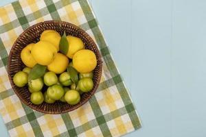 bovenaanzicht van verse, sappige perziken en pruimen op een geruit tafelkleed