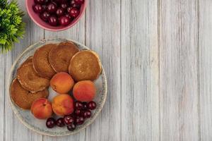 bovenaanzicht van pannenkoeken met abrikozen en kersen