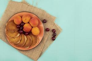 bovenaanzicht van pannenkoeken met kersen en abrikozen foto