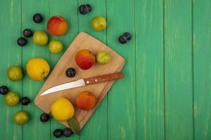 bovenaanzicht van verse perziken op een houten keukenbord