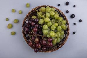 bovenaanzicht van druiven in mand en patroon van druivenbessen op grijze achtergrond