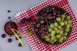 bovenaanzicht van druiven in mand op geruite doek