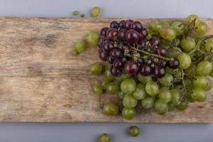 bovenaanzicht van druiven op snijplank op grijze achtergrond met kopie ruimte foto