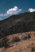 grijze asfaltweg tussen bergen