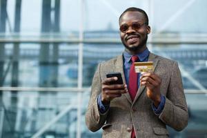 stijlvolle Afro-Amerikaanse zakenman typt informatie van zijn creditcard