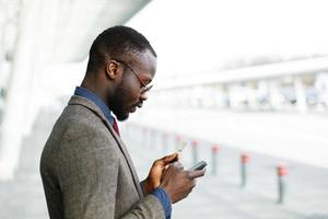 stijlvolle Afro-Amerikaanse zwarte zakenman typt informatie