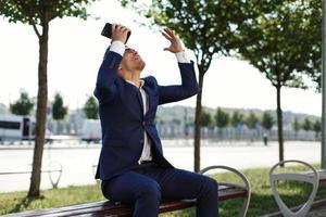 gelukkige jonge zakenman houdt smartphone in zijn arm en schreeuwt