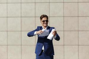 een jonge zakenman die een stuk papier scheurt
