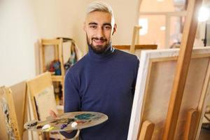 man tekent een schilderij met olieverf en glimlacht