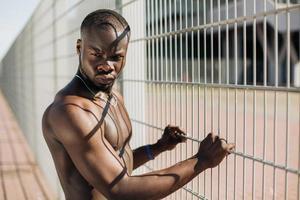 fit man staande bij een hek