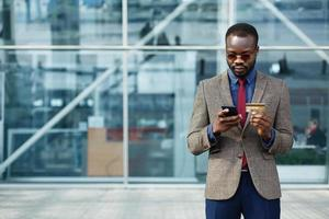 stijlvolle Afro-Amerikaanse zwarte zakenman typt informatie van zijn creditcard
