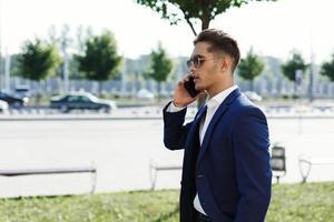 man in een pak lopend en pratend aan de telefoon foto