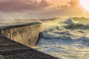 grote golven verpletteren op stenen pier