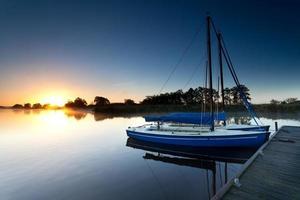 jachten op de pier van het meer bij zonsopgang