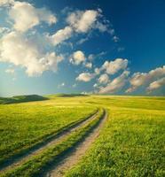 zomerlandschap met groen gras, weg en wolken foto