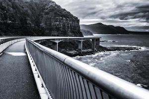 zwart-wit van brug in de buurt van de oceaan