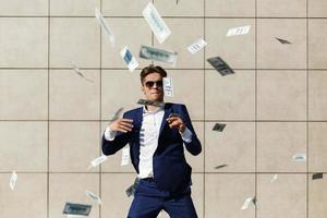 jonge zakenman gooit dollars rond en danst op straat