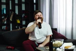 dikke man drinkt bier op de bank