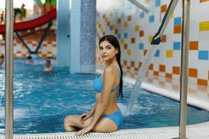 meisje, zittend op de rand van het zwembad