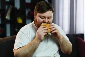 grote man die een hamburger eet foto