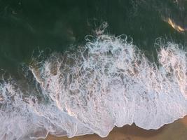 zeegolven die op kust breken