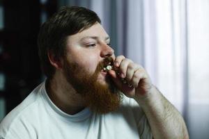 man met popcorn in zijn mond foto