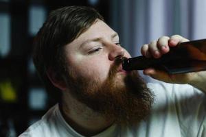 close-up van een man die een biertje drinkt foto