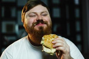 lachende dikke man eet hamburger foto