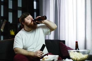 dikke man drinkt bier liggend op de bank