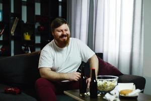 gelukkige dikke man zit op de bank en kijkt tv